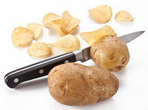 Conceptual image - the knife cuts fresh potatoes Royalty Free Stock Photos