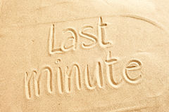 Conceptual image of Last minute holiday deals. For a tropical summer vacation with the text handwritten on golden beach sand Royalty Free Stock Photography
