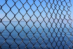 Conceptual image of longed-for freedom seen with metal fencing breaking free on side to open waters beyond. Conceptual image that evokes emotional response with stock image