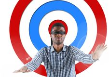 Conceptual image of male executive with black band on eyes against standing archery board Stock Photo
