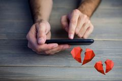 Conceptual image of man hands texting on mobile phone with digital generated red hearts royalty free stock images