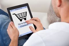 Conceptual image of a man making an online purchase. On his tablet computer with a view of the screen showing a shopping cart and the text for checking out Royalty Free Stock Photos