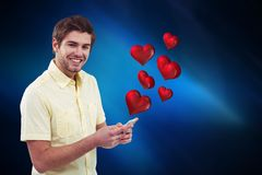 Conceptual image of man texting on mobile phone with digital generated red hearts. Against blue background Royalty Free Stock Photos