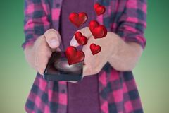 Conceptual image of man texting on mobile phone with digitally generated red hearts Stock Image