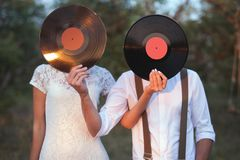 Conceptual Image of Man And Woman Hold A Vinyl Record Discs On Their Faces royalty free stock photos