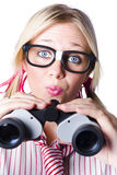 Brainy businesswoman looking to future development. Conceptual image of a nerdy brainy businesswoman making a moue of surprise as she looks through binoculars to Stock Images