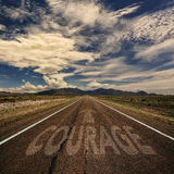 Conceptual Image of Road With the Word Courage. Conceptual image of desert road with the word courage and arrow royalty free stock image