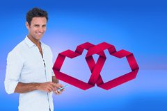 Conceptual image of smiling man texting on mobile phone with digitally generated red hearts Royalty Free Stock Photo