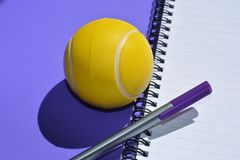Stress ball and pen on an empty spiral bound notebook royalty free stock photos