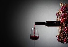 Conceptual image on the theme of winemaking. Red wine pouring from a bottle into a glass. Copy space for your text stock photo