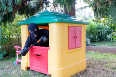 Conceptual image of a thief. Forcing a small toy house using a crowbar stock photography