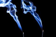 Blue incense smoke forming shapes. Stock Image