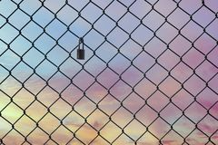 Conceptual image of twilight sky with effect of light pastel tone and steel mesh wire fence. Concept of hope and freedom royalty free stock photo