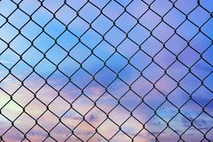 Conceptual image of twilight sky with effect of light pastel tone and steel mesh wire fence. Concept of hope and freedom royalty free stock photos