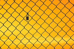 Conceptual image of twilight sky with effect of light yellow tone and steel mesh wire fence. Concept of hope and freedom stock photography