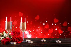 Champagne for couple in love in two flutes on table with red tablecloth royalty free stock image