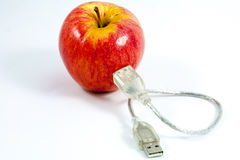 USB cable attached to an apple Stock Photo
