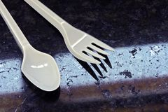 White plastic fork and spoon in contrast with black granite. Conceptual image: white plastic fork and spoon in contrast with black granite Royalty Free Stock Photos
