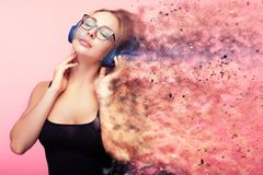 Conceptual image of woman listening to music while she is being. Dispersed in small particles from the feelings she gets from the music. Imagination and Stock Image
