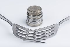 Conceptual imagination of financial greed. Conceptual representation of financial greed by two forks and coins Stock Image