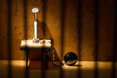 Conceptual jail photo with iron nail ball and chain. Behind out of focus bars stock image