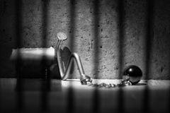 Conceptual jail photo with iron nail ball and chain artistic con. Conceptual jail photo with iron nail ball and chain behind out of focus bars artistic stock images