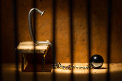 Conceptual jail photo with iron nail ball and chain. Behind out of focus bars royalty free stock images