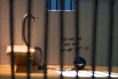Conceptual jail photo with iron nail ball and chain. Behind out of focus bars and window stock photo