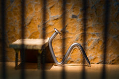 Conceptual jail photo with iron nail sitting behind bars. Conceptual jail photo with iron nail sitting behind out of focus bars royalty free stock images