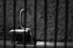 Conceptual jail photo with iron nail sitting behind bars artisti Royalty Free Stock Photos