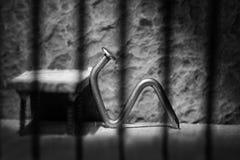 Conceptual jail photo with iron nail sitting behind bars artisti Stock Image