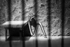 Conceptual jail photo with iron nail sitting behind bars artistic conversion. Conceptual jail photo with iron nail sitting behind out of focus bars artistic stock image