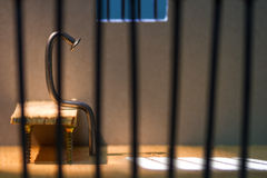 Conceptual jail photo with iron nail sitting behind bars. Conceptual jail photo with iron nail sitting behind out of focus bars and window stock images