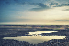 Conceptual landscape image of two people on remote beach with In Stock Photo