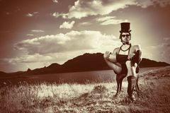 Conceptual man. Fashion shot of a handsome young man posing topless in top hat and bow tie over beautiful landscape Stock Photo
