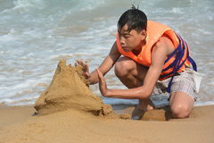 CONCEPTUAL: MAN BUILDS SANDCASTLE AND PROTECTS FROM RISING WATER Royalty Free Stock Photos