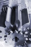 Conceptual metal-idea in blue. Two cogs, gears in connection against patterned-steel Stock Photography