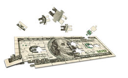Conceptual Money Puzzle. $100 dollar bill jig saw puzzle with pieces flying around Stock Photo