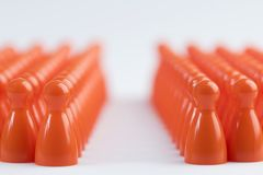 Conceptual orange game pawns in blur stock images