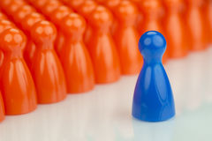 Conceptual orange game pawns and a blue play pawn. As abstract display of inequality in color and number of Stock Photo