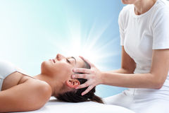 Conceptual osteopathic healing with light glow. Close up portrait of therapist doing healing treatment on young woman.Therapist touching head with light glow in Royalty Free Stock Photo