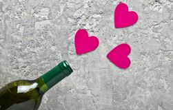 Conceptual photo Bottles of wine and pink decorative hearts. Love, romantic concept, top view. Conceptual photo Bottles of wine and pink decorative hearts. Love royalty free stock images