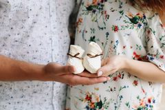 Conceptual photo of couples hands holding baby shoes. Pregnant woman in dress on white background. Conceptual photo of couples hands holding baby shoes in royalty free stock image
