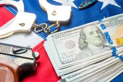 Conceptual photo of the crime and money: dollars, handcuffs and a gun. On the American flag royalty free stock photography