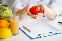Conceptual Photo Of A Female Nutritionist With Fruits On The Des. K Stock Images