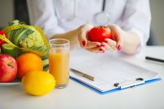 Conceptual Photo Of A Female Nutritionist With Fruits On The Des. K Royalty Free Stock Photography