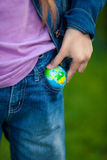 Conceptual photo of girl putting globe in pocket Stock Photos