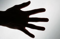 Conceptual photo of a hand ready to take or achieve. Conceptual silhouette hand, ready to take from or achieve Stock Photo