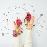 Conceptual photo. Hands with flowers and keys Royalty Free Stock Photos