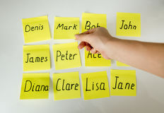 Conceptual photo of hard choice of baby's name. Hand picking papers with names Stock Images